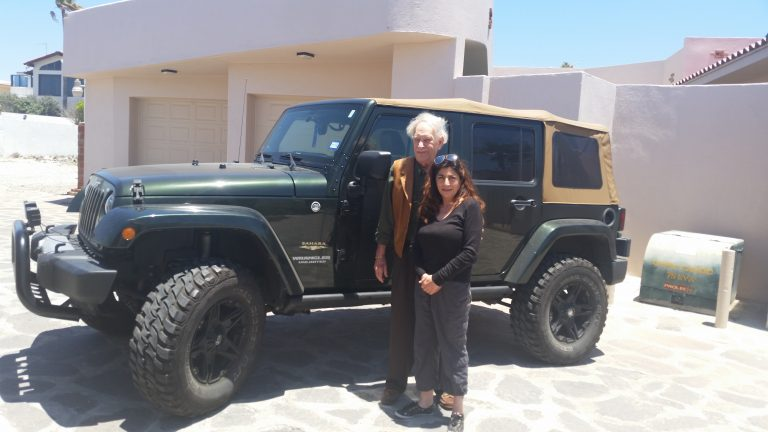 Paul A Weekes and Maria standing by jeep